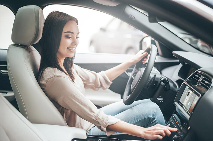 Young-attractive-woman-smiling-and-pushing-buttons-while-driving-a-car