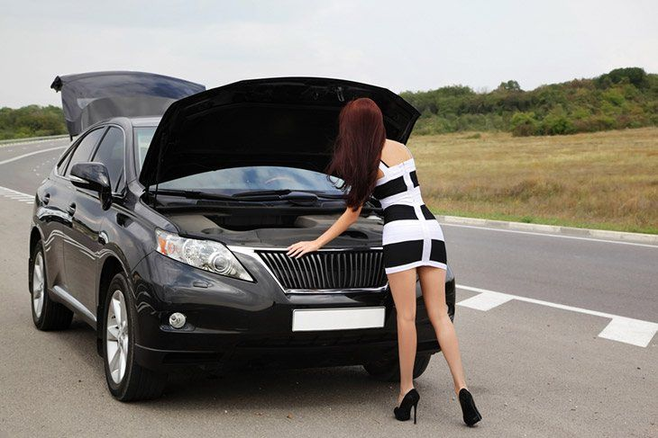 The girl is opening the lid of the car