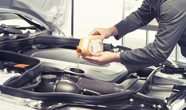 Car-mechanic-replacing-and-pouring-oil-into-engine-at-maintenance-repair-service-station