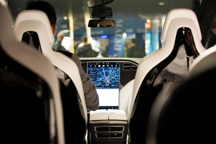 The-interior-of-a-Tesla-Model-X-electric-car-with-large-touch-screen-dashboard.-Seats