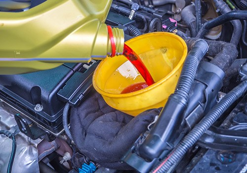 Transmission-oil-fill-up-in-a-car-engine-with-yellow-cone-spire-shape-container